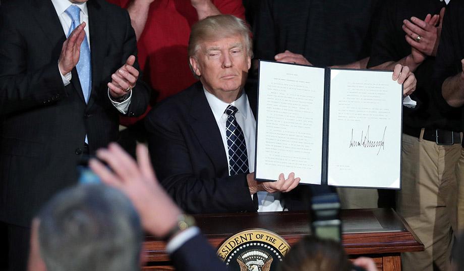 immagine di Trump che mostra la sua firma a una legge
