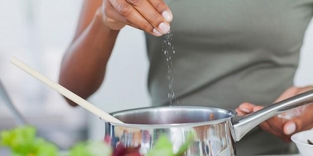 immagine di una persona ai fornelli che aggiunge sale