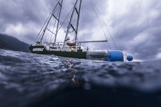 immagine di una bottiglia gigante di plastica in mare