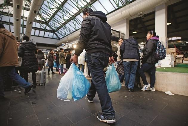 immagine di un uomo di spalle con sacchetti della spesa