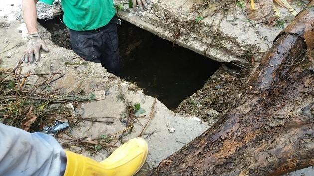 """immagine di operai al lavoro per rimuovere """"tappo"""" nel Canale Nuovo di Lucca"""