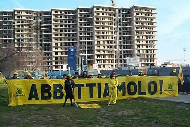 """militanti di Legambiente con lo striscione """"Abbattiamolo"""", sullo sfondo Punta Perotti"""