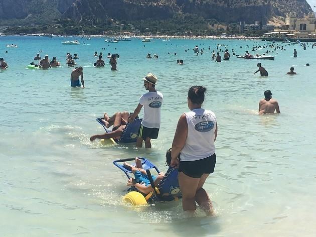 immagine di due disabili accompagnati in acqua a Mondello