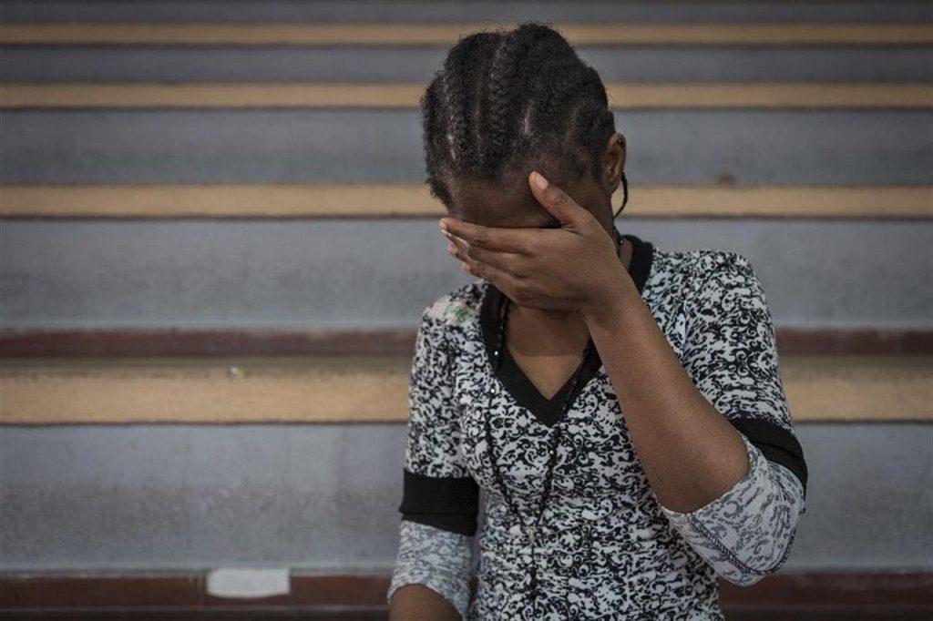 foto di una ragazza nigeriana che si copre il volto con una mano
