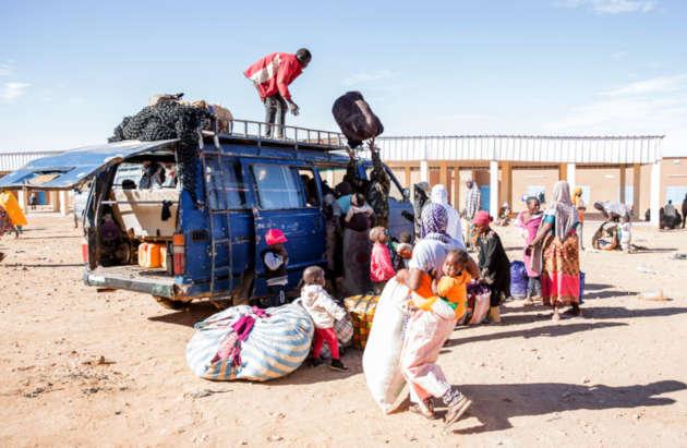 """immagine di migranti In Niger che caricano la propria """"roba"""" su un camion"""
