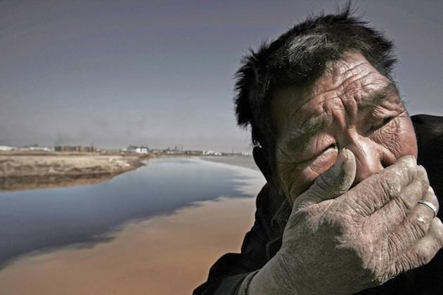 Un uomo in un terreno colpito da siccità
