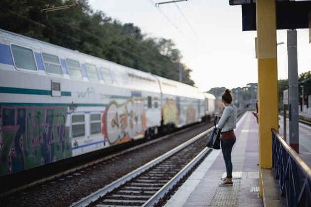 Una ragazza attende l'arrivo di un treno regionale