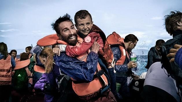 L'immagine di un attivista di una ong che trae in salvo un bambino sbarcato