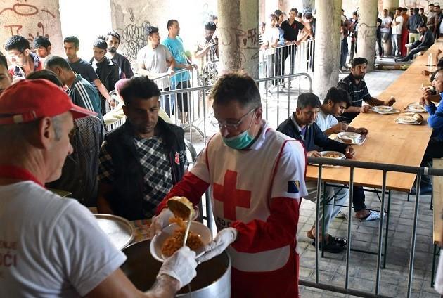 Immagine di migranti in attesa di un pasto a una mensa