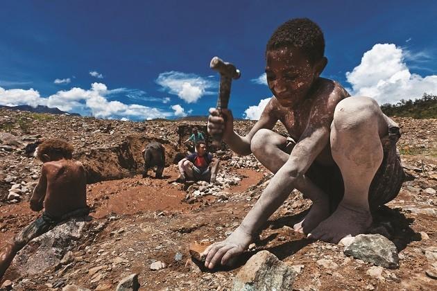 una foto di un bambino che lavora in una miniera in Congo