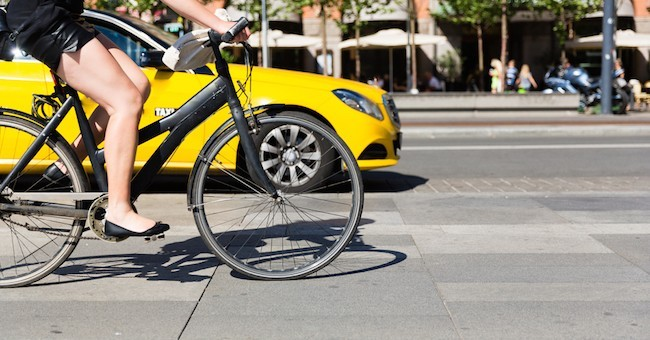 immagine di una donna in bici nel traffico