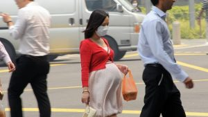 Una donna incinta in una strada inquinata da smog