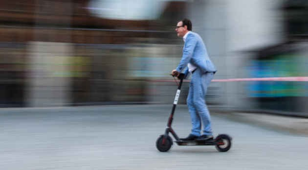 un uomo alla guida di un monopattino elettrico