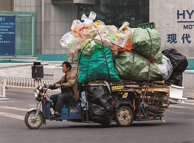 immagine di un ragazzo cinese che trasporta rifiuti su un ciclomotore