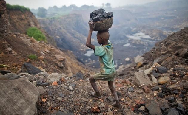 immagine di un minore, di spalle, durante un lavoro pesante