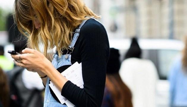immagine di una ragazza mentre guarda il suo smartphone