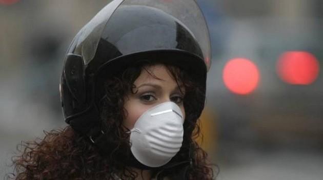 L'immagine di una donna con la mascherina a bordo di una moto