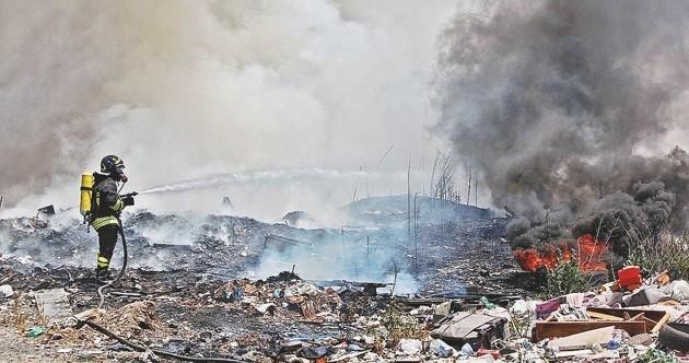 Un vigile del fuoco spegne dei roghi di rifiuti in Campania