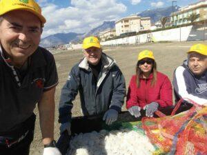 volontari Legambiente raccolgono dischetti di plastica spiaggiati