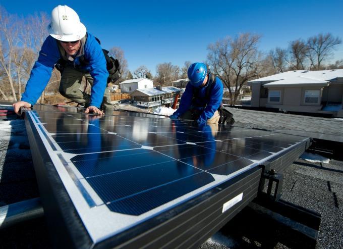 immagine di due operai al lavoro mentre installano un pannello fotovoltaico